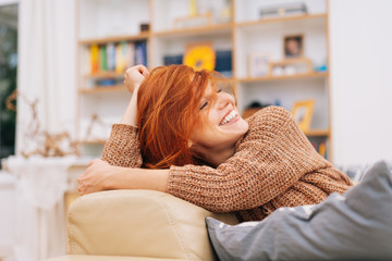 Happy young woman leaning back on a couch