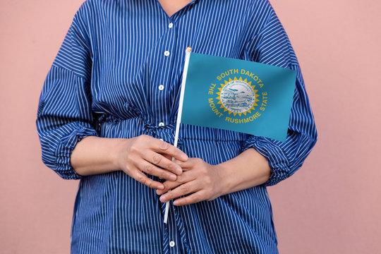 South Dakota state flag. Close up of a woman's hands holding South Dakota flag.