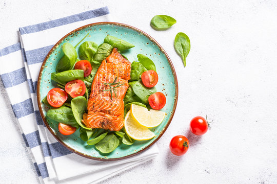 Baked salmon fish fillet with fresh salad top view on white.