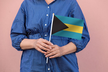 Bahamas flag. Close up of a woman's hands holding Bahamas flag.
