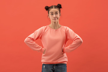 Why is that. Beautiful female half-length portrait isolated on trendy coral studio backgroud. Young emotional surprised, frustrated and bewildered woman. Human emotions, facial expression concept.