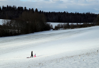 A man and a child walk back up after sledging down a hill after a snowfall at the Chalet-a-Gobet in Lausanne