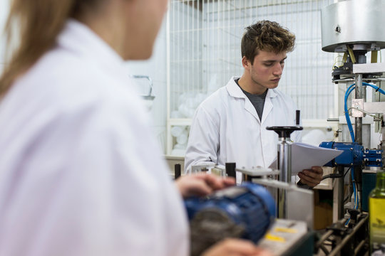 Young caucasian man with white coat working in a factory