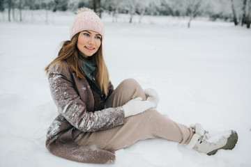 Photo of blonde sitting in snow on walk in winter forest