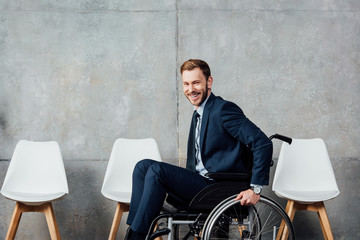 smiling businessman sitting in wheelchair in waiting hall and looking at camera