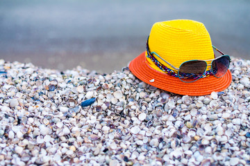 Fashionable hat with glasses are on the sea shells. Concept of tourist recreation on the sea beach