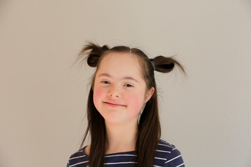 Cute smiling down syndrome girl on the grey background