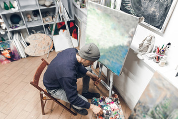 Creative man sits in a studio on a chair near a clean host, mixes a paint on a palette and paints a new painting. Top view. Creating an oil painting at home in the studio