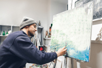 Happy creative artist sits on the chair at the studio and works on the picture and smiles. Positive artist paints oil painting. Painting Concept.