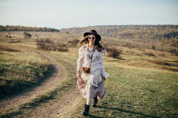 Beautiful young boho woman walking on nature