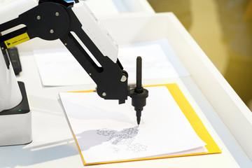 Robotic hand with a pencil draws simple graphic drawings on white paper. Future and art concept.