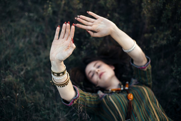 Beautiful boho girl lying on grass with hands up