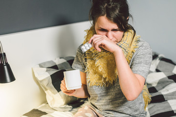 Young beautiful Caucasian woman has a cold, flu with high fever and heat at home in bed. The girl takes headache pills with a glass of water, a bitter pill is crooked.