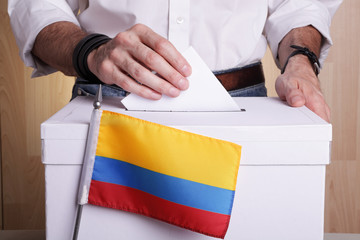 A Colombian citizen inserting a ballot into a ballot box. Colombia flag in front of it