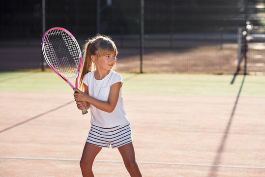 Little female tennis player in white uniform concentrating and focusing on the training before game. Sunlight background.