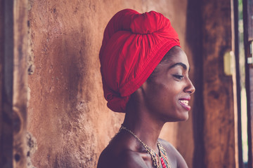 African beauty traditional girl smiling and looking - beautiful portrait for pretty woman with black skin - tradition dress and nude skin - attractive afro lady face with rural wall in background