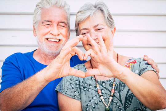 Love and valentine's day concept for cheerful happy couple of senior man and woman caucasian people together doing hearth with hands and smile - happiness after life together forever
