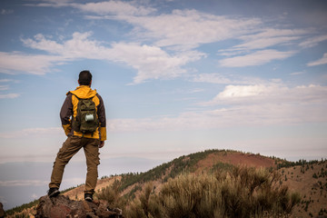 Lonely man in trekking adventure discover activity at the mountain with backpack - hiker looking the landscape and anjoying the wild undiscovered nature - beautiful environment for vacation
