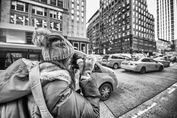 Female photographer taking pictures of New York Cabs in winter