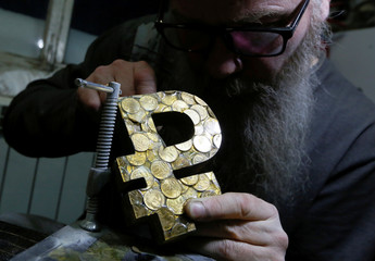 Russian artist Slonov works on his artwork depicting the sign of the Russian rouble in Krasnoyarsk