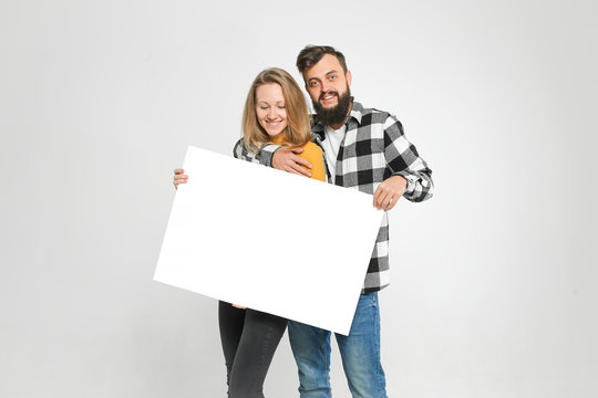 young loving couple, bearded man and blondie are smiling, hugging, holding blank banner, isolated on white background, Advertisement concept. Mockup for design