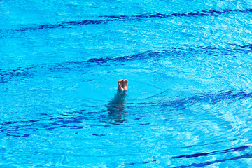 Feet of woman doing a handstand inside swimming pool