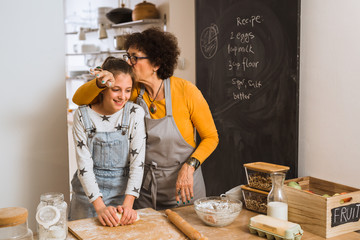 happiness is homemade. senior woman kissing her granddaughter while baking in kitchen