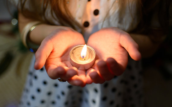 Burning candle in the palms of a girl