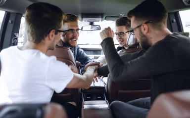 men greet colleagues before leaving by car.