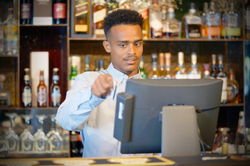 Registration male of bartender employee of a new order by a cash register. The barman pays the order with a credit card. Service concept.