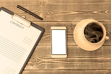contract, pen, smartphone, coffee Cup on wooden table background. the concept of the coffee break, the signing of the contract. business.