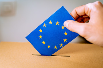 Election in European Union - voting at the ballot box. A hand putting an EU flag vote in the ballot box. Wall mural