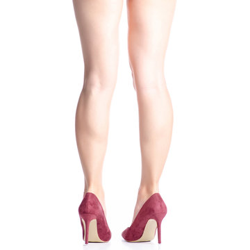 Female legs in red maroon high heel shoes on white background. Isolation