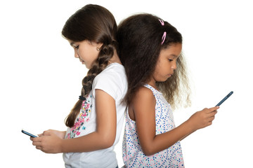 Two small girls staring at their smartphones