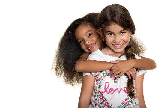 Cute hispanic and african-american small girls hugging