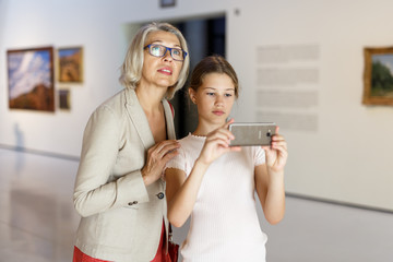 People using phone in museum