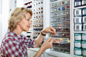 Mature glad woman customer picking various buttons