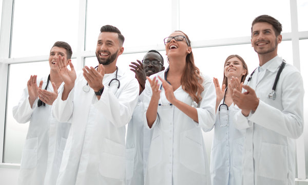 fellow doctors are applauding and smiling