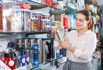 Young female customer choosing ware for wine bottle in household shop
