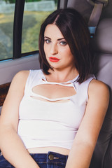 Young beautiful brunette girl in the car salon