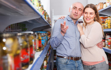 Man and woman choosing pickles goods