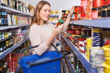 Woman choosing preserved goods in food store