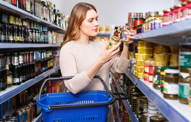 Positive female customer with basket holding canned goods in the food store