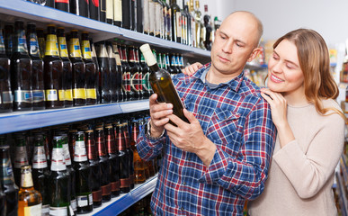 Family couple choosing alcohol products in hypermarket