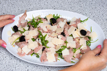 Carpaccio salad. Medium roast beef with parmesan, olives and fresh herbs on a plate. Female hands holding a plate with salad. Concept healthy food.