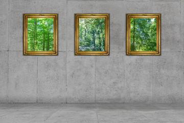 Zimmer aus grauem Beton mit Bildern in goldenen Rahmen