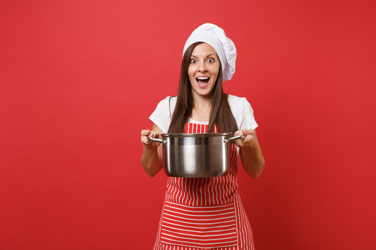 Housewife female chef cook or baker in striped apron white t-shirt toque chefs hat isolated on red wall background. Smiling surprised woman holding vacant crockery pot. Mock up copy space concept.