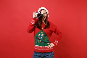 Smiling young Santa girl in sweater, Christmas hat taking pictures on retro vintage photo camera isolated on red background. Happy New Year 2019 celebration holiday party concept. Mock up copy space.