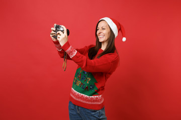Smiling young Santa girl in Christmas hat doing taking selfie shot on retro vintage photo camera isolated on red background. Happy New Year 2019 celebration holiday party concept. Mock up copy space.