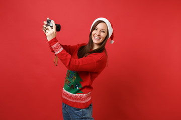Pretty young Santa girl in Christmas hat doing taking selfie shot on retro vintage photo camera isolated on red background. Happy New Year 2019 celebration holiday party concept. Mock up copy space.